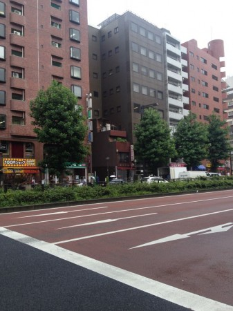 To the right of the 100 Yen shop, a taller building is built around a smaller one.